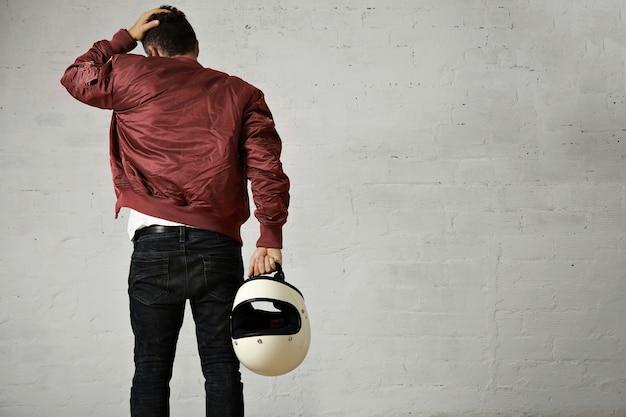 Plan arrière d'un jeune motocycliste en jeans, blouson militaire et tenant son casque blanc touchant ses cheveux isolé sur blanc