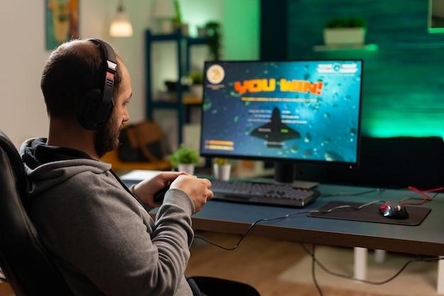 Plan arrière d'un joueur professionnel jouant à un jeu de tir en ligne sur un ordinateur à l'aide d'une manette sans fil. un joueur compétitif gagnant un tournoi de jeux vidéo utilise un équipement professionnel dans un studio de jeu à domicile