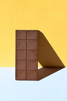 Plan avant d'une barre de chocolat noir avec des ombres dures, fond jaune et bleu, conceptuel