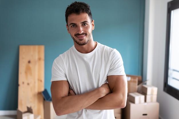 Plan d'un beau jeune homme debout regardant la caméra tout en se reposant de la fabrication de boîtes pour le déménagement dans un nouvel appartement.
