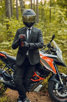 Plan d'un beau mec vêtu d'un costume et d'un casque posant avec un vélo de sport sombre dans la forêt.