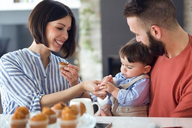 Plan de beaux jeunes parents avec leur bébé en train de manger des muffins à la maison.