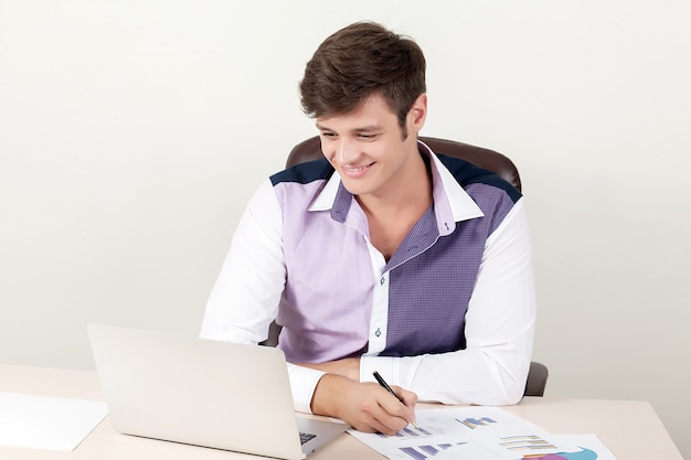Plan d'un bel homme d'affaires directeur créatif travaillant au bureau assis au bureau avec un ordinateur portable.