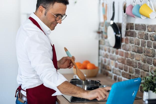 Plan d'un bel homme cuisinant en suivant une recette sur la tablette numérique dans la cuisine à la maison.