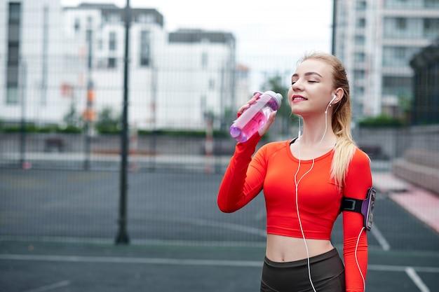 Plan d'une belle coureuse debout à l'extérieur tenant une bouteille d'eau. fitness femme prenant une pause après avoir exécuté la séance d'entraînement