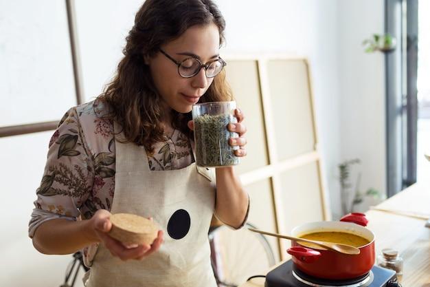 Plan d'une belle femme cuisinant et sentant les bons arômes d'épices dans une casserole en magasin bio.