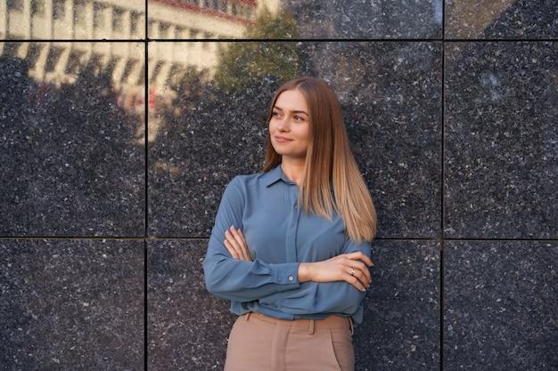 Plan de la belle jeune femme d'affaires portant une chemise en mousseline de soie bleue en position debout avec les bras croisés sur un mur de marbre gris
