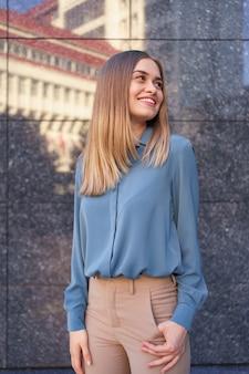 Plan de la belle jeune femme d'affaires portant une chemise en mousseline de soie bleue en position debout et posant sur un mur de marbre gris