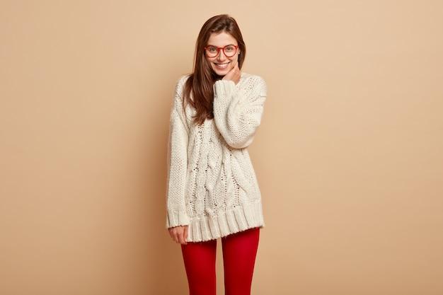 Plan d'une belle jeune femme sourit et pose à l'intérieur, a un sentiment de bonheur, entend des nouvelles positives, vêtue d'un pull blanc et de collants rouges, montre des dents parfaites, profite d'une belle journée de congé
