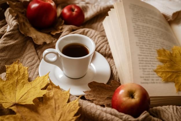 Plan de café expresso près d'un livre ouvert avec une feuille d'érable jaune comme signet entouré de pommes rouges
