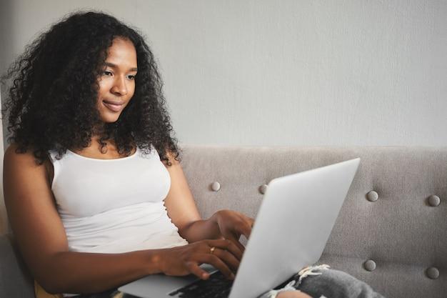 Plan candide d'une jeune traductrice métisse concentrée avec des cheveux noirs volumineux tapant sur un ordinateur portable, traduisant un article, ayant un regard concentré. technologie et freelance