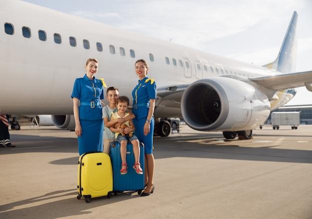 Plan complet de deux enfants heureux assis sur leurs bagages devant un gros avion un jour et souriant à la caméra avec de belles hôtesses de l'air. famille, voyage, concept de vacances