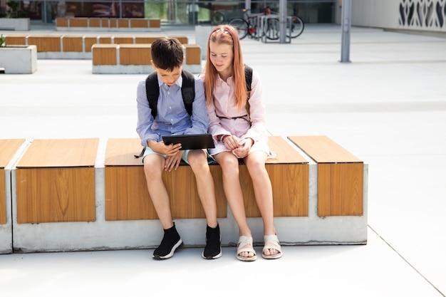 Plan complet de deux jeunes frères et sœurs adolescents utilisant une tablette numérique près de l'école, faisant leurs devoirs