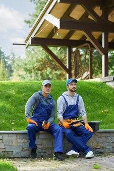 Plan complet de deux jeunes ouvriers en uniforme faisant une pause, assis à l'extérieur en train de prendre un café