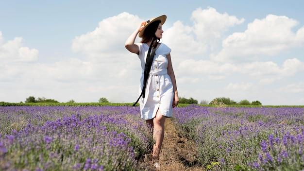 Plan complet d'une femme dans un champ de fleurs