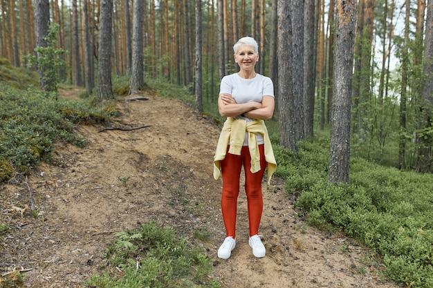 Plan complet d'une femme mature active avec des cheveux blonds et un corps en forme debout sur un sentier en forêt portant des vêtements de sport, se reposant pendant l'entraînement, gardant les bras croisés. personnes, activité et âge