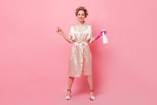 Plan complet de femme en peignoir tenant martini et nettoyant