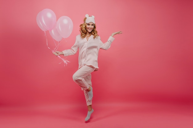 Plan complet d'une fille d'anniversaire en chaussettes grises posant. portrait de jeune femme souriante en pyjama de soie sautant avec des ballons roses.