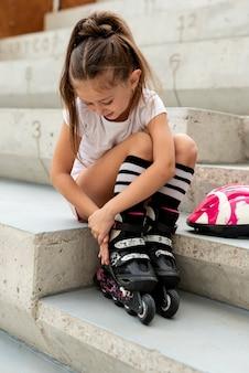 Plan complet d'une fille qui met des patins à roues alignées