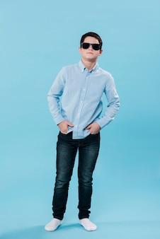 Plan complet d'un garçon moderne posant avec des lunettes de soleil