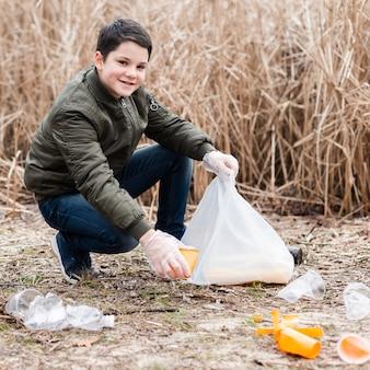 Plan complet d'un garçon nettoyant le sol