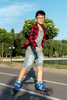 Plan complet d'un garçon avec des patins à roues alignées