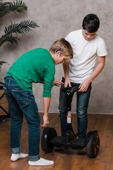 Plan complet de garçons utilisant un hoverboard