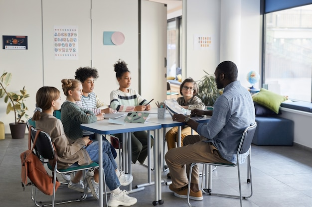 Plan complet d'un groupe diversifié d'enfants assis à table avec un enseignant dans une salle de classe moderne