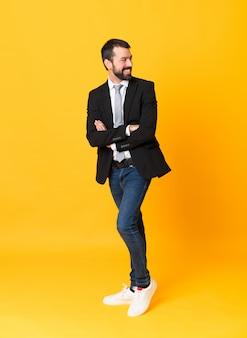 Plan complet d'homme d'affaires isolé jaune avec les bras croisés et heureux