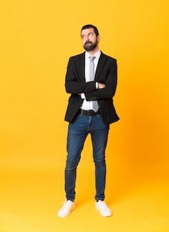 Plan complet d'homme d'affaires isolé sur jaune avec une expression de visage confuse