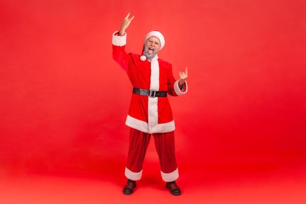 Plan complet d'un homme âgé excité avec une barbe grise portant un costume de père noël montrant du rock and roll chanter devant la caméra et crier avec un regard fou. studio intérieur tourné isolé sur fond rouge.