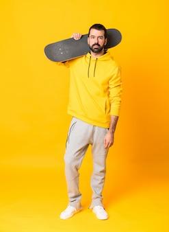Plan complet de l'homme au jaune isolé avec un patin