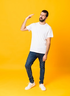 Plan complet d'un homme à la barbe isolé jaune avec une expression fatiguée et malade