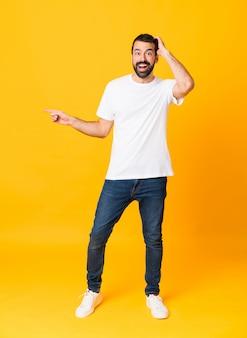 Plan complet d'un homme à la barbe isolé sur un jaune surpris, un doigt pointé sur le côté