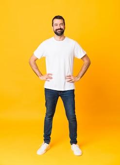 Plan complet de l'homme à la barbe sur jaune isolé posant avec les bras à la hanche et souriant