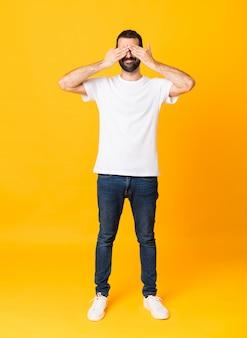 Plan complet d'un homme avec une barbe sur un mur jaune isolé couvrant les yeux à la main