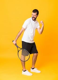Plan complet d'un homme isolé sur un terrain jaune où il joue au tennis et célèbre une victoire