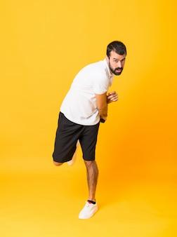 Plan complet d'homme jouant au tennis sur un mur jaune isolé