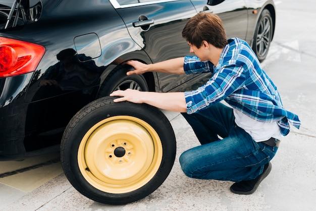 Plan complet d'un homme qui change de pneu de voiture