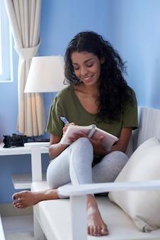 Plan complet de la jeune femme prenant des notes assis sur un canapé