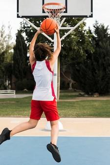 Plan complet d'une jeune fille jetant dans le panier de basket