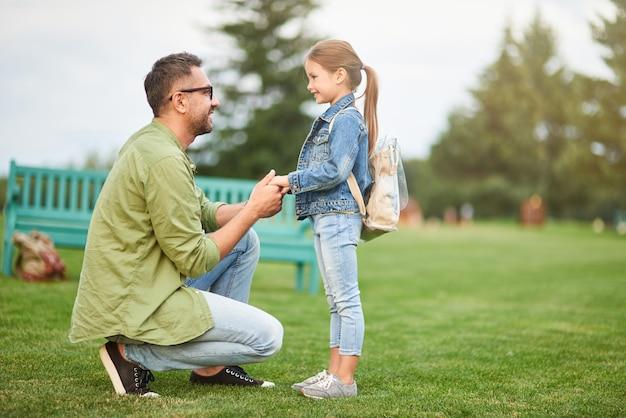 Plan complet d'un jeune père heureux tenant les mains de sa fille papa passant du temps avec son mignon