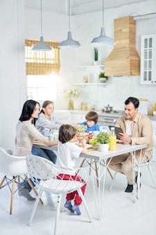 Plan complet d'une joyeuse famille hispanique savourant un repas ensemble tout en déjeunant, assis à table dans la cuisine à la maison. enfance, concept de manger