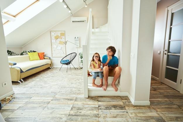 Plan complet d'un petit frère et d'une soeur portant des lunettes assis dans les escaliers et faisant