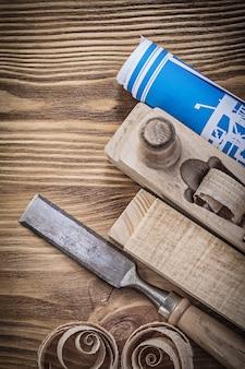 Plan de construction bleu raboteuse ciseau plat copeaux de bois sur planche de bois vintage