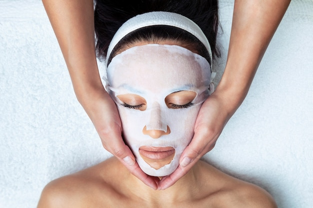 Plan d'un cosmétologue fabriquant le masque facial à la vitamine c pour le rajeunissement d'une femme au centre de spa.
