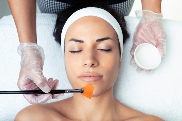 Plan d'un cosmétologue faisant un peeling chimique pour rajeunir le visage d'une femme au centre de spa.