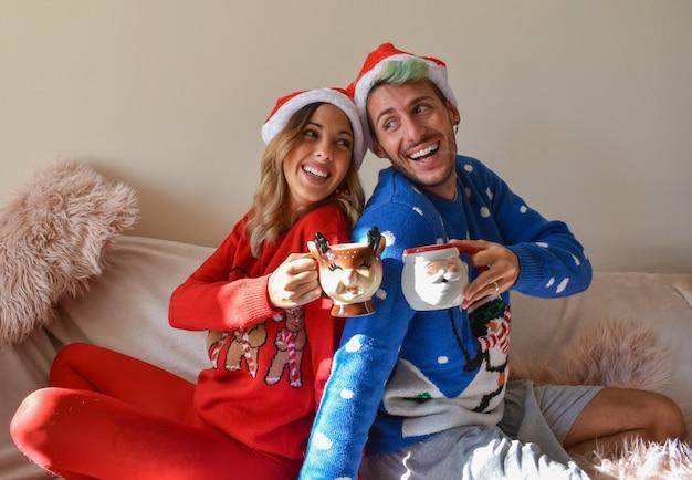 Plan d'un couple heureux dans des huttes de noël et des vêtements tenant des tasses drôles