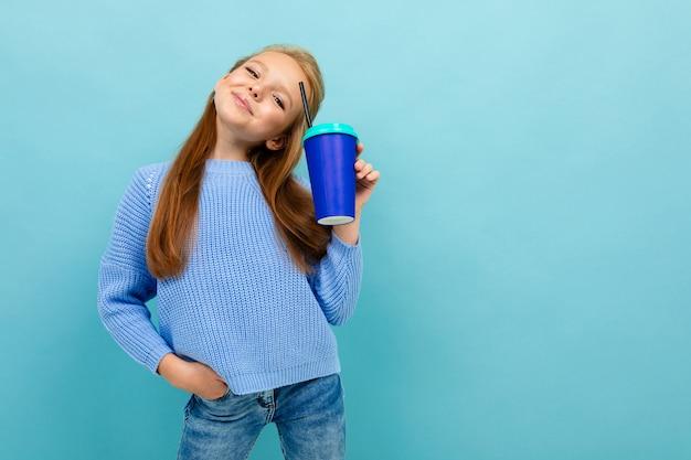 Plan demi-longueur d'une écolière joyeuse heureuse avec une tasse de papier dans ses mains contre un mur bleu