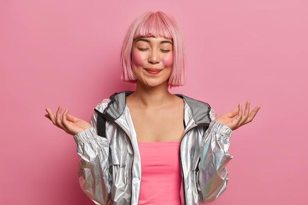 Plan demi-longueur d'une femme asiatique heureuse lève les mains, se tient les yeux fermés, se sent heureuse, imagine quelque chose d'agréable, porte une veste d'argent